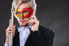 Man in carnival mask playing flute Stock Images
