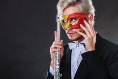 Man in carnival mask playing flute Royalty Free Stock Image
