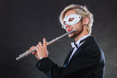 Man in carnival mask playing flute Royalty Free Stock Images