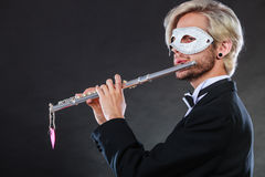 Man in carnival mask playing flute Royalty Free Stock Photography