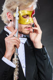 Man in carnival mask playing flute Stock Photo