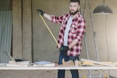 The man is a carpenter, a builder, a designer stands in the work. Shop, holds a roulette in his hands. On table laptop and construction tools, in background a royalty free stock photography