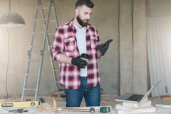 Man is carpenter,builder,designer stands in workshop, holds cup. Of coffee and uses smartphone. On desk is laptop and construction tools, in background a stock image