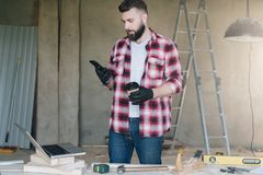 Man is carpenter,builder,designer stands in workshop, holds cup stock photography