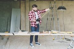 The man is a carpenter, a builder, a designer stands in the workshop, holds a roulette in his hands. Around there are construction tools, in the background a Royalty Free Stock Photography