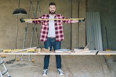 The man is a carpenter, a builder, a designer stands in the workshop, holds a roulette in his hands. Around there are construction tools, in the background a Stock Image