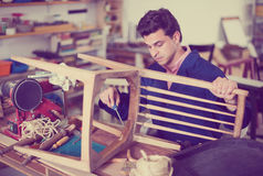 Man carpenter in furniture repair workshop Stock Image