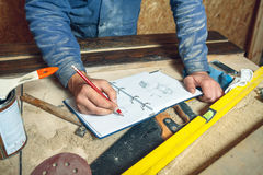 Man carpenter in his home manufactory. Man carpenter in his home studio working with wood and draws sketches in pencil in a notebook Royalty Free Stock Images