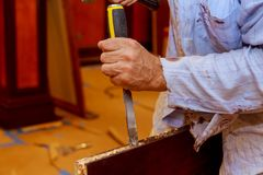 Man carpenter makes a hole in the wooden a door for a hammer and chisel. Close-up stock images