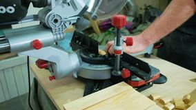 A man carpenter is working with wood using a special machine in a studio. The joiner uses a circular saw machine stock footage
