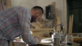 A man in a carpentry workshop makes calculations at the table stock footage
