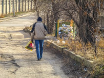 Man carries bag of trash to a dumpster Stock Photography