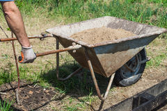 A man carries clay in the wheelbarrow stock image
