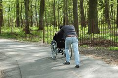 Man carries a disabled person in a wheelchair royalty free stock images
