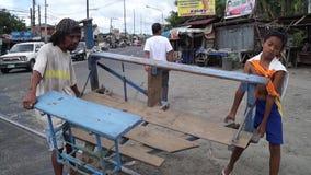 Man carries foot driven passenger trolley cart across the highway. San Pablo City, Laguna, Philippines - November 5, 2012: Man carries foot driven passenger stock footage
