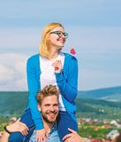 Man carries girlfriend on shoulders, sky background. Romantic date concept. Woman holds heart on stick symbol of love. Couple in love walking outdoor sunny day stock image