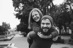 Man carries his girlfriend on the back Stock Images