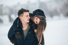 Man carries his girlfriend on the back. In the park, in winter holidays royalty free stock photography