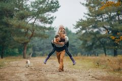 Free Man Carries His Wife And Daughter On His Back At Forest Path Next To Dog During Walk Stock Photos - 122364953