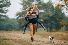 Free Man Carries His Wife And Daughter On His Back At Forest Path Next To Dog During Walk Stock Images - 122364954