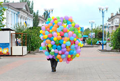 Man carries Many bright balloons Stock Photos