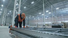 Man carries metal construction in new modern industry warehouse.  stock footage
