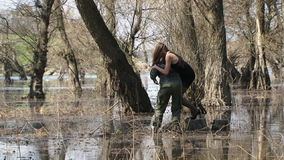 Man Carries Model On Shoulders To Stump In Flood. This is a moving video shot of a strong bald man in khaki clothes carrying a young pretty model in short black stock footage