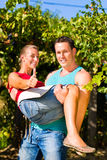 Man carries woman on his arms in vineyard Royalty Free Stock Images