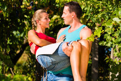 Man carries woman on his arms in vineyard Royalty Free Stock Photography