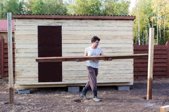 Man carries wooden beam near the barn Stock Photography