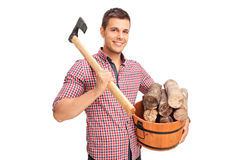 Man carrying axe and holding a bucket with logs Stock Photo