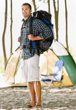 Man carrying backpack at campsite Royalty Free Stock Photography