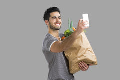 Man carrying a bag full of vegetables Stock Photography