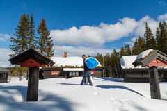 Man carrying bags in deep snow to a traditional cabin Stock Images