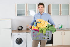 Man Carrying Basket With Heap Of Clothes Royalty Free Stock Photos