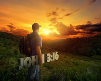 Man carrying Bible verse. A man carrying a Bible verse while walking in the mountains at sunset Royalty Free Stock Image