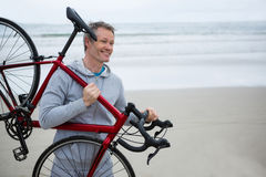 Man carrying bicycle on beach Stock Photography