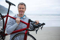 Man carrying bicycle on beach stock photos