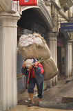 Man carrying big sack on street, morning view of Darjeeling, India as of April 12, 2012 Stock Image