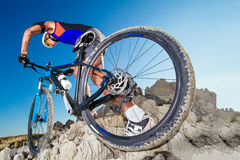Man carrying a bike on the rocky terrain Stock Images