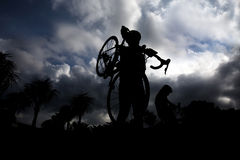Man carrying  bike. Silhouettes of man carrying  bike while walking at sunset Royalty Free Stock Photography