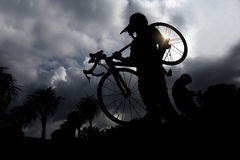 Man carrying  bike. Silhouettes of man carrying  bike while walking at sunset Royalty Free Stock Photos