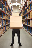 Man Carrying Boxes In Warehouse. Man Carrying Three Boxes In Warehouse Stock Photography