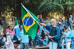 Man carrying the Brazil Flag at the celebration of the 119 years. Campo Grande, Brazil - August 26, 2018: Civic Parade desfile civico at 13 de Maio street. Man royalty free stock photos