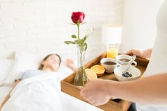 Man Carrying Breakfast Tray For Woman Sleeping In Bed. Cropped image of men carrying breakfast tray for women sleeping in bed at apartment Royalty Free Stock Photo