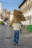 Man carrying brooms Stock Photo