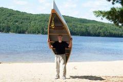 Man carrying a canoe Stock Photos