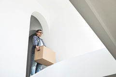 Man carrying cardboard box in new home Royalty Free Stock Photos
