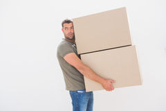 Man carrying cardboard moving boxes at home Stock Photos