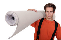 Man carrying carpet Stock Image